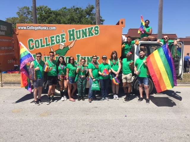 College Hunks Hauling Junk team members posing with rainbow flags and beads (and a moving truck).