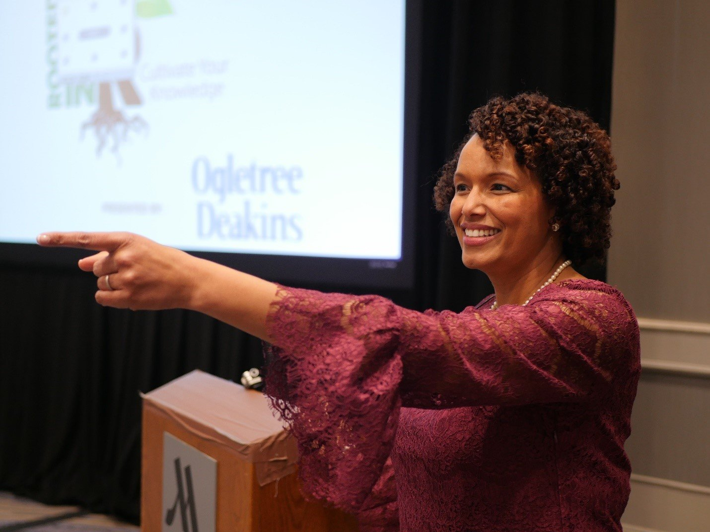 Heather Younger, speaking in a conference setting, gesturing to the attendees.