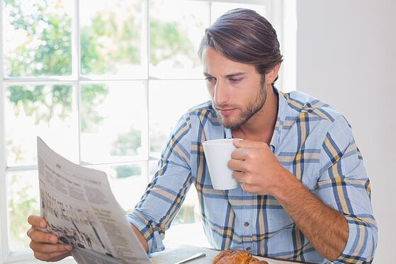 Casual man having coffee while reading newspaper at home in the living room.jpeg