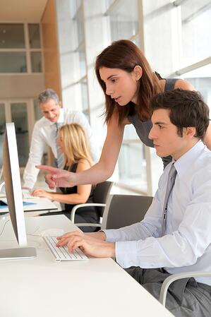 Image of an office mentor pointing to colleague's screen