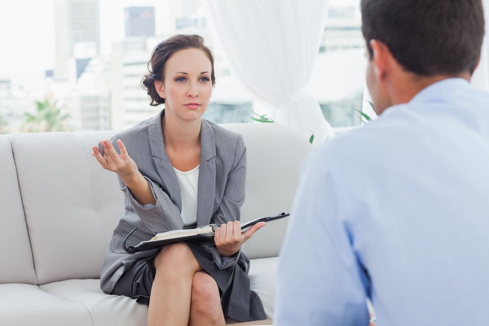 Serious businesswoman interviewing a candidate in a bright office
