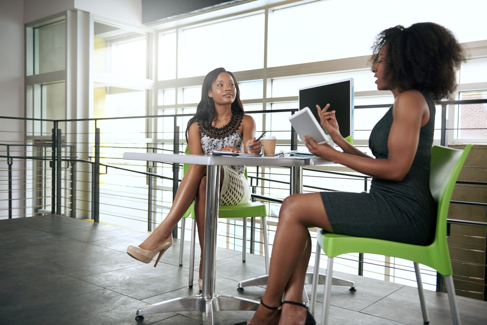 Two women discussing benefits of having an employee engagement strategy