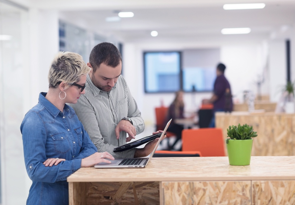 business team in modern bright office interior looking at retention numbers on laptop and tablet computer