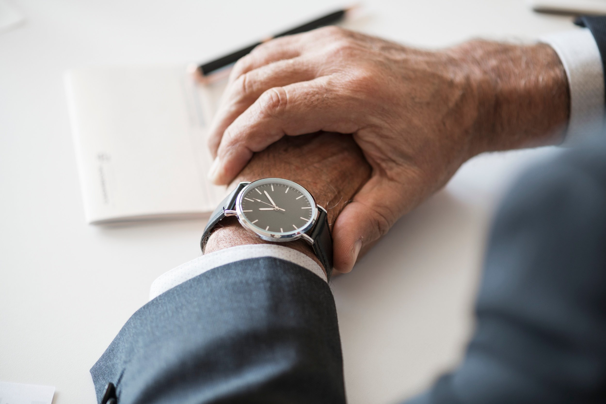 An image focused on a wristwatch, on the wrist of a person wearing a business suit. Image source: https://stocksnap.io/photo/VL9LPY5XWL