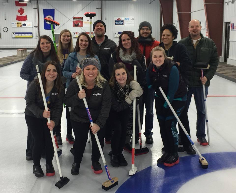 dogIDs team members pose with curling brooms at a curling rink.