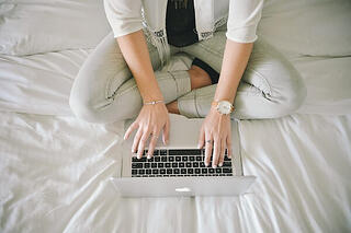 Woman cross-legged on bed, working from home on a laptop