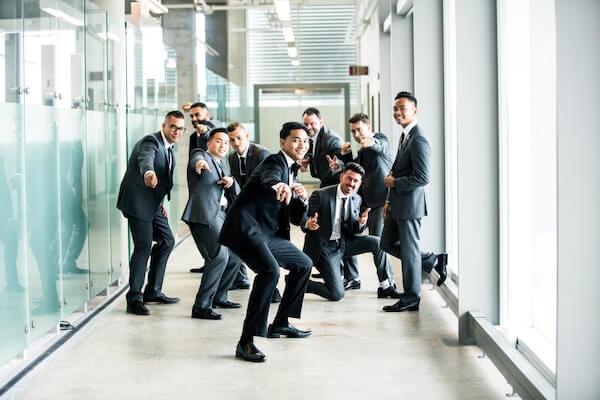 men in suits all looking happy in hallway