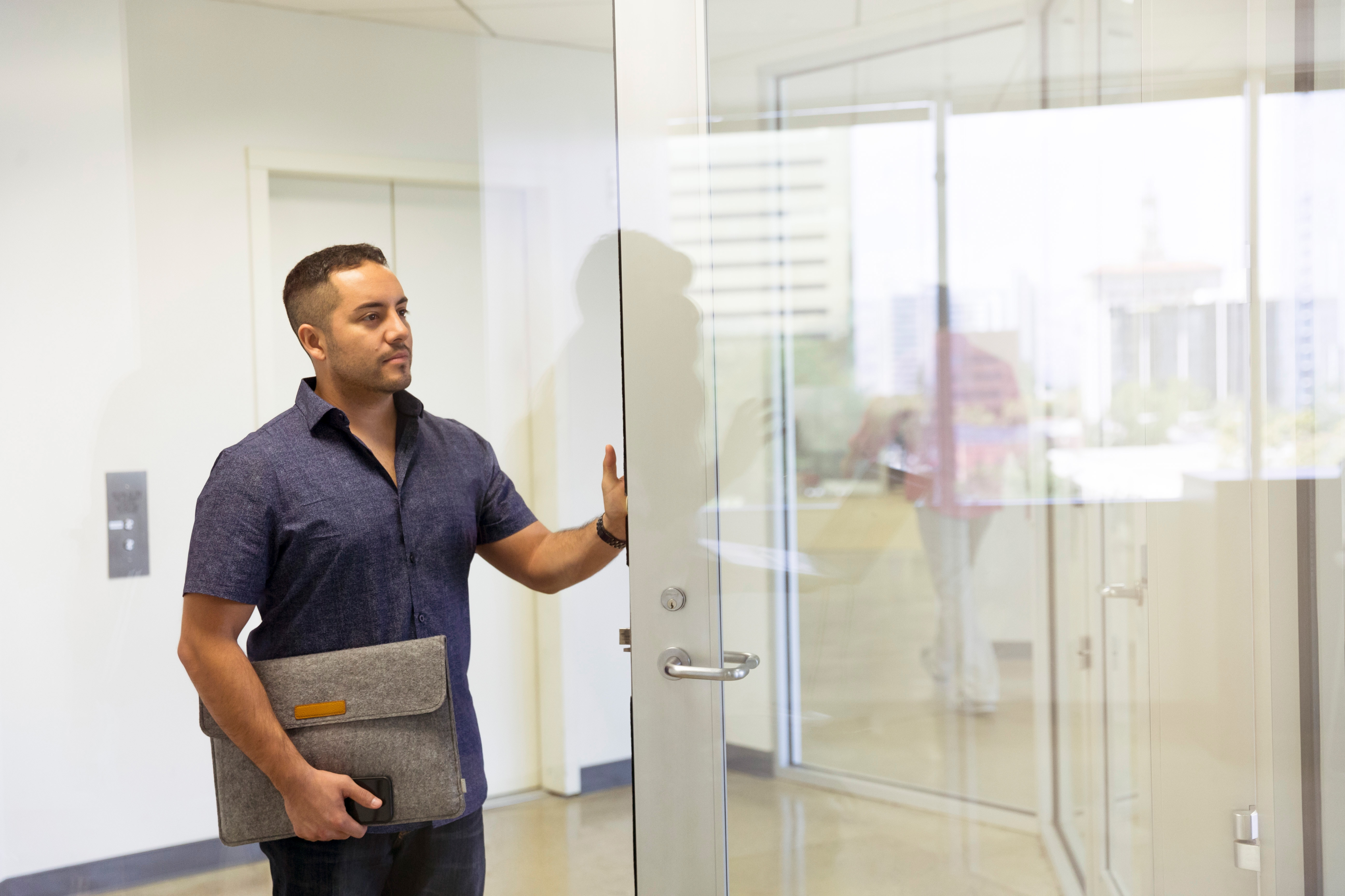 An employee opening a door, as if leaving a workplace. Image source: https://unsplash.com/photos/8nGuPyGkOMI