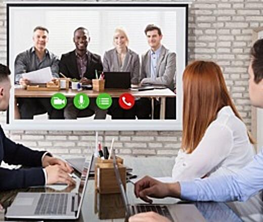 Coworkers place a video call from office to office, with workers at a conference table looking at a screen featuring workers on a wall.