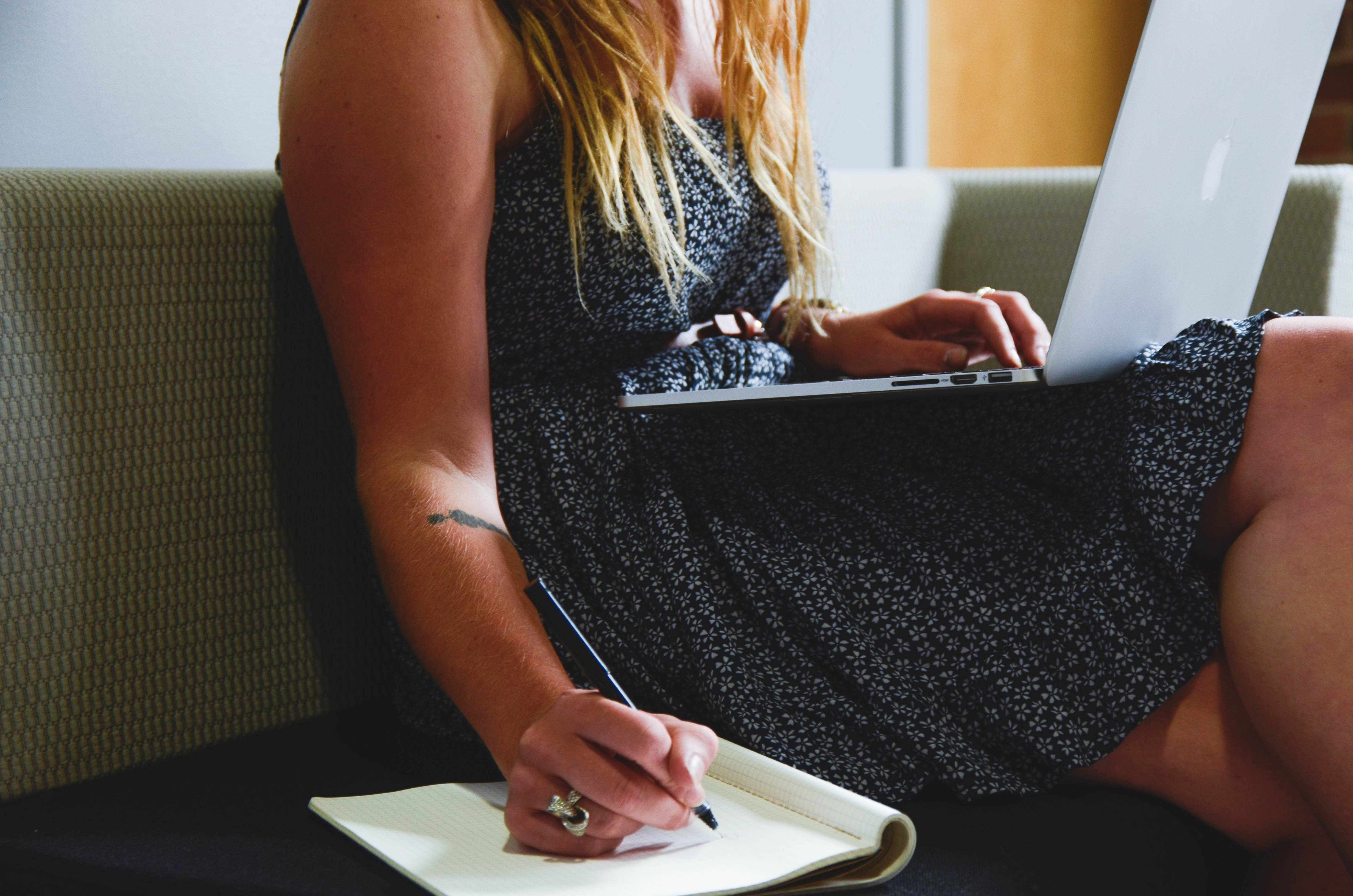 A woman seated on a couch using a laptop writes on a notepad with her free hand.