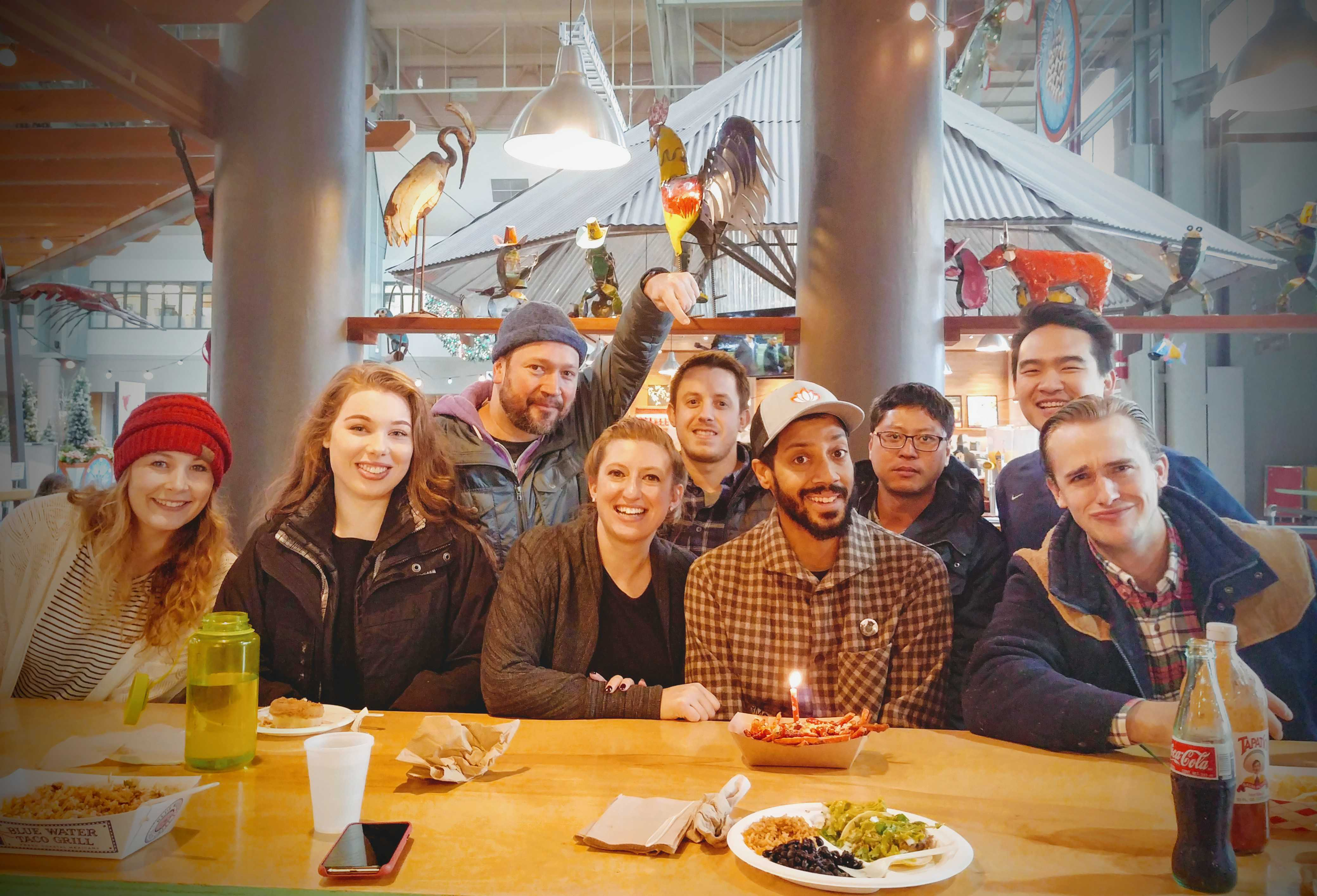 Tyler and work friends celebrating his first work anniversary with a candle in some fries.