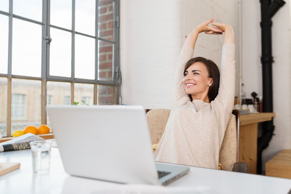 Happy relaxed young woman sitting at a desk with a laptop in front of her stretching her arms above her head and looking out of the window with a smile