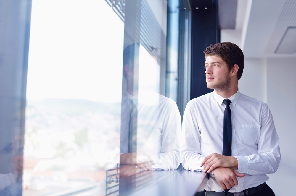 happy young business  man work in modern office looks at his reflection in the window