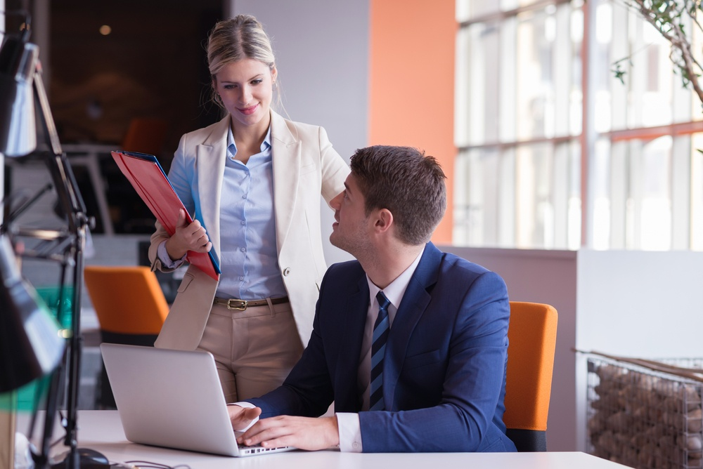 woman mentoring fellow coworker and working in modern bright office indoor