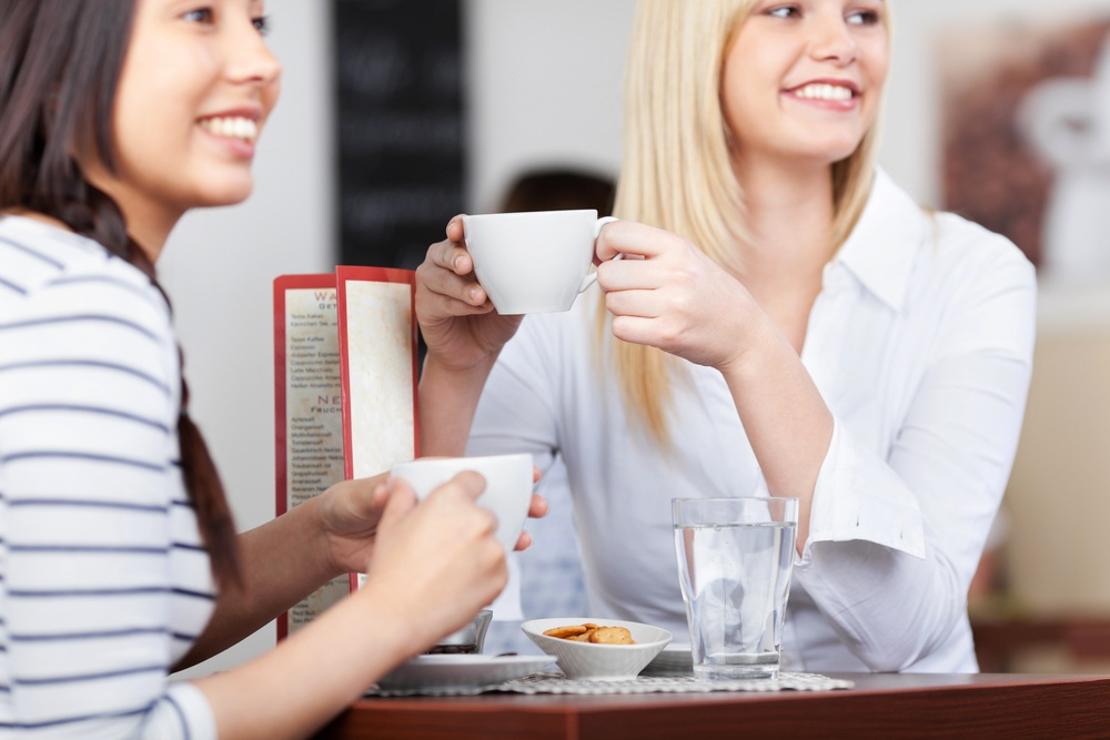 young people in cafe sitting at table and relaxing with a cup of coffee